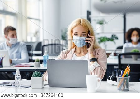 Working In Modern Office After Returning From Quarantine. Millennial Lady In Protective Mask Speaks