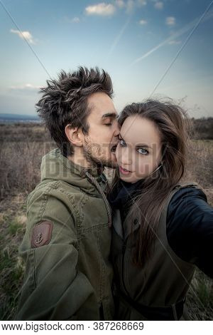 Portrait Of Young Man, Who Is Biting Woman\'s Face. Woman Is Looking In To Camera. Couple Is Stretch
