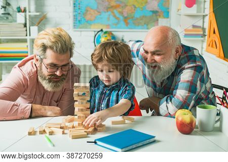 Father And Son With Grandfather Was Excited With Playing Game. Grandfather Father And Son Playing In