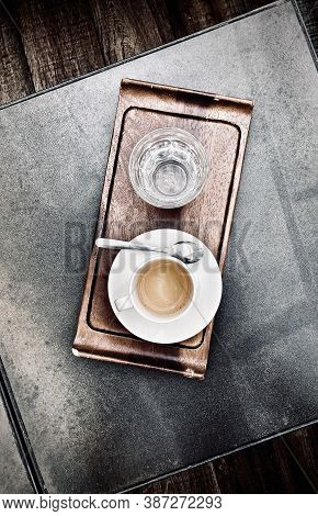 Freshly Brewed Coffee In Cup With Saucer And Spoon Placed Next To It. Everything Is On Stylish Woode