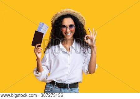 Ready For Travel. Happy Brunette Woman With Passport And Tickets Gesturing Ok Sign Over Yellow Backg