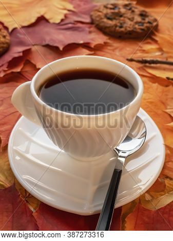 White Cup Of Coffee With Saucer On Autumn Maple Leaves And Cookies Covered With Chocolate Pieces, Wa