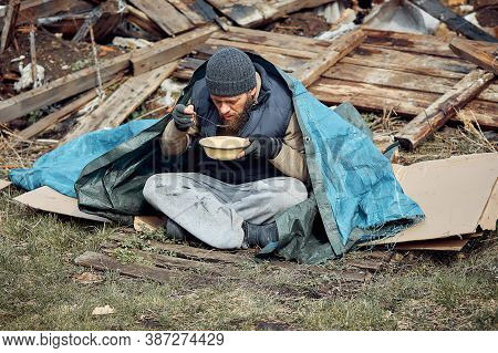 A Homeless Man Eats Soup From A Plate Near The Ruins, Helping Poor And Hungry People During The Epid