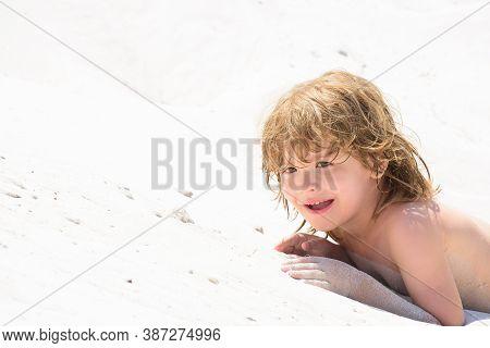 Happy Child Boy Play With Sand In The Sea. Kid Tan, Suntan. Gentle Kids Skin Tanning