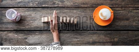 Wide View Image Of Female Hand Stopping Collapsing Dominos In A Conceptual Image Of Business Crisis