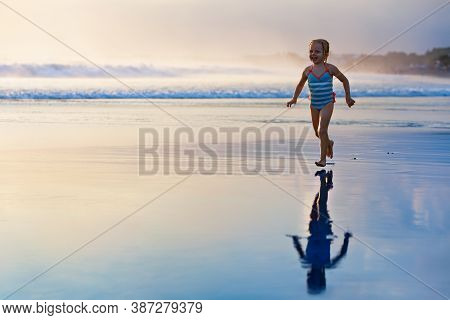 Happy Family Have Fun On Tropical Sea Beach Resort. Funny Baby Girl Run With Splashes By Water Pool