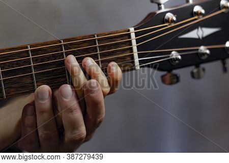 An Adult's Hand Helps A Child Play The Am Chord On The Guitar Fretboard.