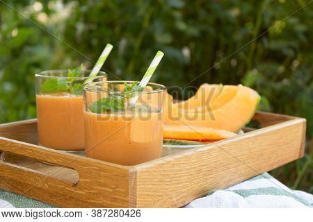 Two Glasses Of Fresh Cantaloupe Smoothie With Mint Leaves On A Wooden Tray In The Garden. Cantaloupe