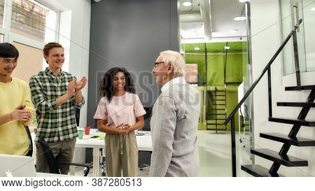 Aged Man, Senior Intern Looking Pleased While His Colleagues Praising Him On First Day At Work, Frie