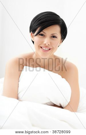 Halfnaked woman hugs the eiderdown, isolated on white background