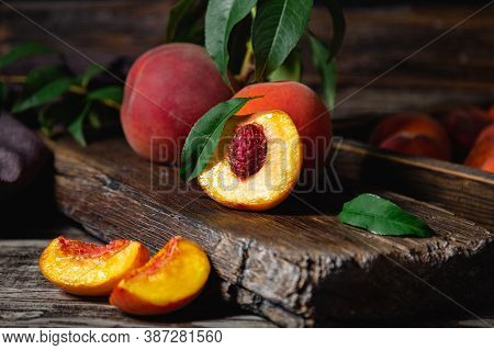 Peaches With Leaves On Dark Wooden Board With Peach In Halves With Peach Seed Stone. Composition Wit