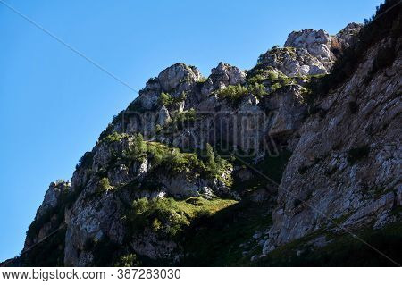 Beautiful Cliff Ledges With Grass And Trees Against Blue Sky