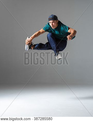 Cool B-boy Jumps Isolated On Gray Background. Dance School Poster. Breakdance Lessons