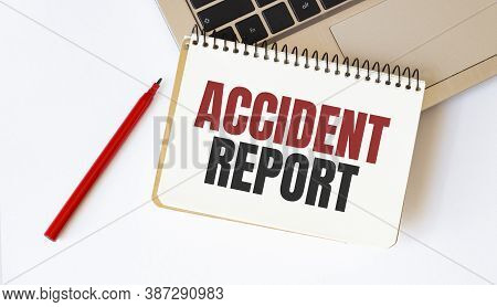 Laptop, Red Pen And Notepad With Text Accident Report In The White Background