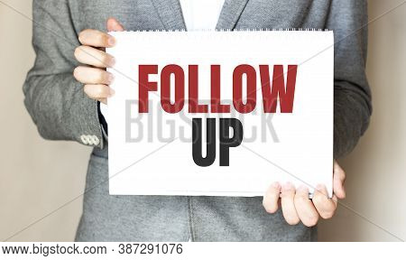 Businessman Holding A Card With Text Follow Up