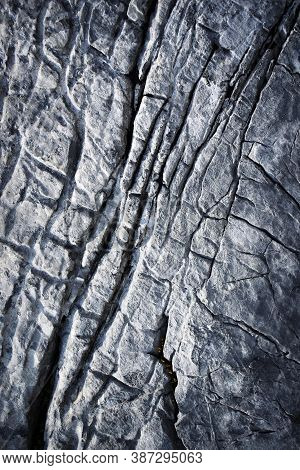 Abstract Background Detail Of A Dark Limestone Structure With Grooves