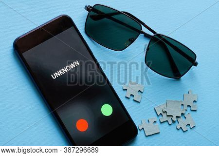 A Black Smartphone With An Undecided Unknown Challenge Lies On A Blue Surface Next To A Puzzle And S
