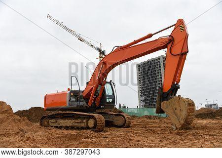 Excavator During Excavation At Construction Site. Backhoe On Earthworks. Heavy Construction Equipmen