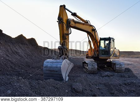 Excavator During Excavation At Construction Site On Sunset Background. Red Backhoe On Road Work. Hea