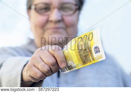 Satisfied, An Elderly Adult Woman Gives A Currency Of Close-up 200 Euros. Mature Woman And Holds Out