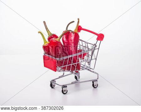 Red Chili Peppers In A Food Basket On Wheels. Red Peppers On A White Background