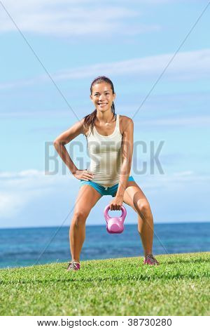 fitness exercise woman lifting kettlebell during strength training exercising outdoors on grass by the ocean. Beautiful young fit fitness instructor doing one-arm kettlebell swing or snatch.