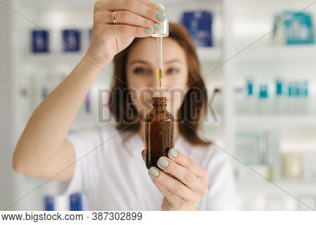 A Female Doctor-cosmetologist In A White Coat Holds A Bottle Of Enriched Argan Oil In Hands. Woman W