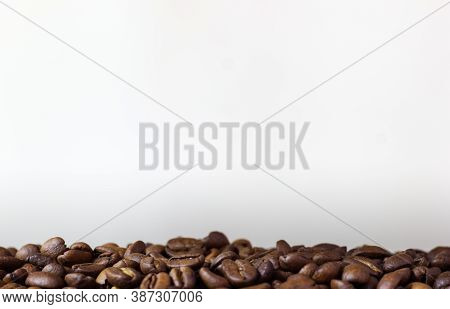 Roasted Coffee Beans On White Background. Heap Of Coffee Beans. Poured Coffee Close Up. White Patter