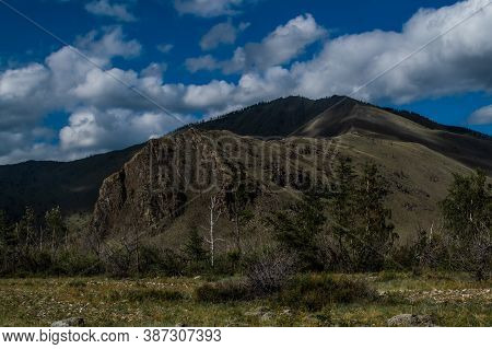 Mountain Range On Baikal, Sarma. Large Tall Green Grassy Rock. Trees And Bushes In The Foreground In