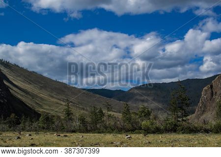 Mountains On Baikal, Sarma. Large Tall Green Grassy Rock Near Gorge. Trees And Bushes In The Foregro