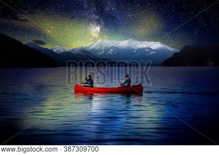 Adventurous People On A Red Canoe In A Lake. Night Sky With Stars And Northern Lights. Dream Mood. L