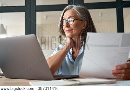 Smiling Mature Middle Aged Business Woman Using Laptop Working On Computer Sitting At Desk. Happy Ol