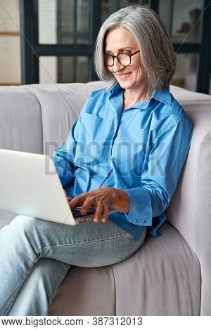 Happy 60s Older Mature Middle Aged Adult Woman Holding Laptop Using Computer Sitting On Couch At Hom
