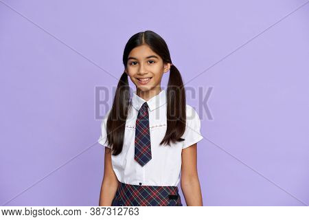 Smiling Smart Indian Hispanic Preteen Girl With Ponytails Wearing School Uniform Standing Isolated O