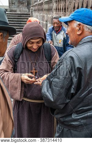 Quito, Ecuador - December 2, 2008: Historic Downtown. Closeup Of Young Monk In Brown Habit Cuts Nail