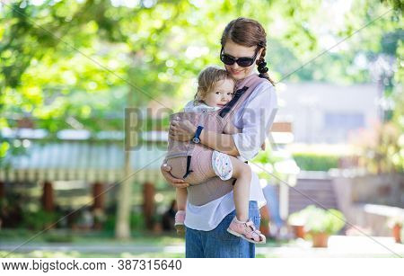 Caucasian Woman And Her Daughter In Baby Carrier In Summer Park
