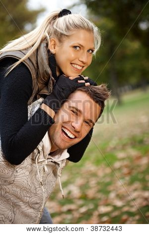 Autumn portrait of beautiful young smiling couple having fun in park.