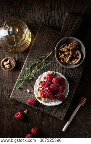 Brie Or Camembert Cheese With Raspberries, Honey And Walnuts . Selective Focus, Dark Background, Top