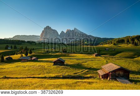 Chalets At Seiser Alm, High Altitude Meadow With Langkofel Mountain In Background At Sunrise, Dolomi