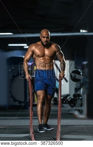 Portrait Of Fit Strong Athletic Man Pulling Rope In Fitness Club