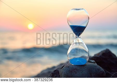 Hourglass With Sand Standing On Rock. Sunset Over Sea And Nature Landscape. Running Of Time And Rela