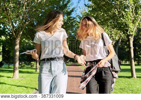 Two Beautiful Happy Girls Teenagers 17, 18 Years Old Walking Together In Park, Girls Laughing Talkin