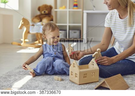 Joyful Young Nanny And Little Kid Playing With Wooden Blocks In Cozy Nursery Room