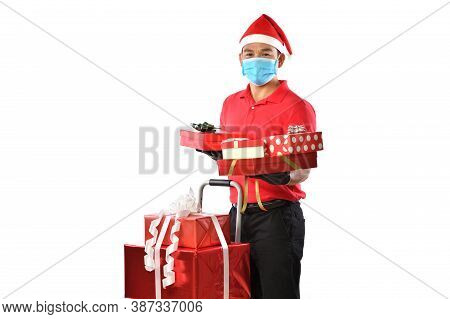 Happy Young Asian Delivery Man In Red Uniform, Medical Face Mask, Protective Gloves, Christmas Hat C