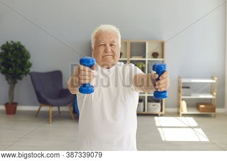 Senior Man Leading Active Lifestyle Exercising With Dumbbells In His Living-room