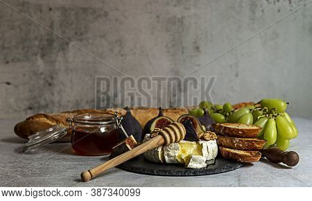 Oven Baked Camembert Cheese With Honey, Figs, And Fresh Baguette. Delicious Gourmet Snack