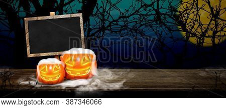 Halloween Background.pumpkin With Smoke On Grunge Blackboard On Wood Table At Spooky Dead Tree And F