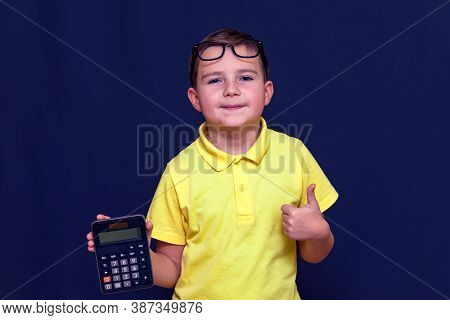 Close Up Attractive Young Schoolboy With Eyeglasses, Yellow T-shirt Holds A Calculator, Shows Thumb