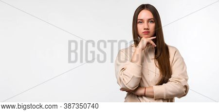 Photo Of Pensive Young Woman With Long Chestnut Hair Standing With Hand Raised On Chin And Looking T