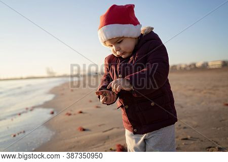 Caucasian Toddler Child In Santa Hat On The Beach. Traveling On Holidays